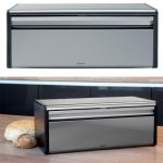 silver-and-black-brabantia-bread-box-and-fall-front-with-fingerprint-proof-and-matt-steel-on-the-wooden-table-near-small-breads