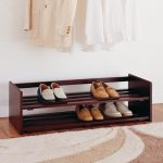 simple and open shoes and boot storage idea with desk style beneath white wall and wooden floor and patterned area rug