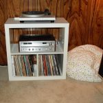 simple and small ikea stereo cabinet design with bookshelf in the bedroom beneath wooden siding wall