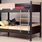simple low profile bunk bed design with yellowish bedding and stairs and black patterned pillow and red sheet and area rug