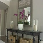 simple-mirrored-candle-holders-for-the-hallway-on-the-table-with-drawers-and-mirror-hang-on-the-wall-combined-with-purple-flowers