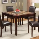 simple square granite dining table set in dark finishing featuring brown leather dining chairs and white rug area on wooden floor plus candleholders and pictures on wall
