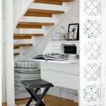 simple white understairs home office idea with carved siding and wooden staors and stripe area rug and wooden bench and wooden floor