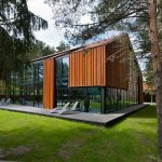 single storey forest house design with glass and wooden siding and grassy meadow and concrete front foyer
