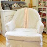 slip cover for chair in white with striped accent plus bookshelf and light wooden floor