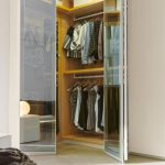 small walk in dressing room idea with beige wooden storage and glass door