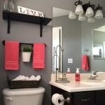 soft and fashionable coral color design above rattan basket with black wooden vanity with wall mirror and track light
