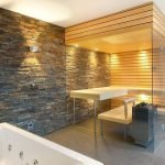spacious and luxurious bathroom with walk in sauna and white tub and stone wall accent