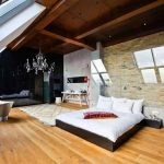 spacious loft bedroom design with skylight and wooden floor and bath and chandelier and fireplace