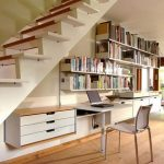 spacious understairs home office idea with wall bookshelves and small desk and floating file cabinet and wooden floor and concrete white stairs