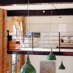 stunning home with loft area with double height ceiling and arched brick window and green vault pendants