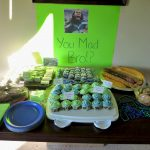 super bowl party decoration idea with picture and message and cupcakes and pastry on wooden table
