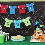 super bowl party decoration idea with uniform on wire decoration on black board and flag on hamburger on green table
