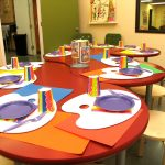 super large and stylish curving art table for kids idea in red color with creamy stools with canvas and color palette