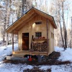 super small rustic cabin design with black roof and wooden door and log storage