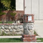 sweet combination of stone and red brick mailbox idea with mini garden on green grassy meadow before a house