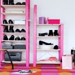 sweet pink shoes and boot storage idea with colorful area rug and white painted wall and table and bag