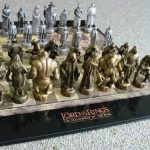the-Lord-of-the-rings-chess-set-with-white-and-gold-pieces-standing-on-flat-chessboard-on-the-grey-carpet