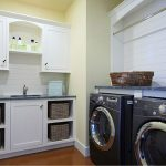 tidy and livable laundry room idea with washing and drying machines and white wall and basket shelves and wooden floor