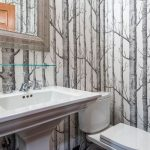 tree-birch-wallpaper-design-for-bathroom-with-white-water-closet-and-white-sink-with-brown-framed-mirror