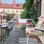 Tropical Balcony Idea With Wooden Flooring And Black Metal Fence And Colorful Cair And Rainbow Rug And Table And Vertical Garden