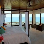 tropical dream private house bedroom wth open plan and ocean view and black sofa with white beddig and canopy bed and ceiling fan