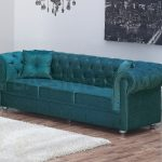 turquoise velvet fabric sofa design with tuft pattern and small cushion on wooden floor with wall palette