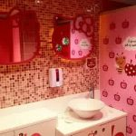 two-red-hello-kitty-wall-mirror-on-small-squares-wall-with-pink-wallpaper-and-red-door-also-white-bathroom-furniture