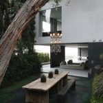 unique and simple backyard patio design with wooden rustic table and bench and shrub aside modern home idea