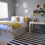 vintage bedroom decor idea with white bedding and stripe patterned area rug and white tabe and wall racks and yellow and gray combination