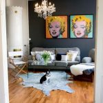 vintage retro style of living room with seductive marilyn monroe pictures on gray wall with gray sofa and white vintage chair and faux leather throw and wooden floor