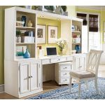 wall unit with shelves desk under cabinets and under drawer system a white chair with cushion an area rug