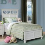white full size toddler bed with striped bedding and wooden nightstand plus modern rug on wooden floor and green drapes