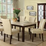 white granite dining table set in six classy dining chairs in white plus soft rug and light wooden floor and cute flower centerpieces