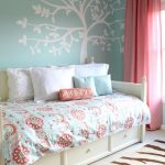 white indoor daybed with under drawer system and light blue bedding with red flower pattern some decorative pillows in white and light teal colors