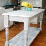white-kitchen-island-from-a-sofa-table-near-white-kitchen-cabinet-also-yellow-flowers-and-orange-fruit-also-brown-wooden-floor