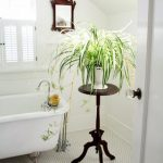 white loft bathroom idea with freestanding tub and honeycomb flooring and tripod table and potted plant and glass window