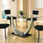 wonderful all glass dining table in rectangle shape with unique legs and black chairs on wooden floor and glass window