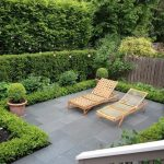 wonderful backyard patio design with wooden pool chairs and concrete patio and shrub and wooden fence and potted plants