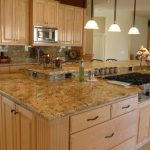 wonderful kitchen design with large wooden island with cooktop beneath white pendants with river gold granite idea
