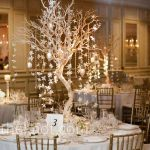 wonderful-wedding-centerpieces-with-votive-candles-and-garlands-of-orchids-and-crystals-hang-down-from-tall-Manzanita-trees-from-modern-wedding-in-chicago-and-by-theknot.com