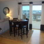 4 chairs and square table for dining room with white and black drapes and brown rug on wooden laminate floor
