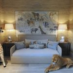 A sofa bed furniture in white with animal pillowcases animal map wall decoration a pair of bedside table with table lamps two large animal stuffs near the furniture