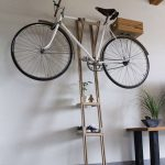 A tinny leaning ladder wood rack with bike rack on its top