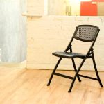 Black Folding Chair In Room With Wooden Floor Stone Wall And White Stairs