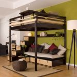 Black painted wooden loft bed with stairs and daybed plus pillows a floor light fixture