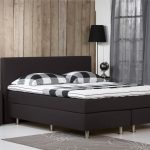 Black Spring Box Designed By IKEA Idea Black Bed Frame With Black Headboard  Black Minimalist Bedside Table With Black Glass Top A Floor Lamp In Black Grey Bedroom Rug With Flower Motif
