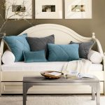Classic styled daybed in white with mattess and accent pillows a smaller grey table white area rug