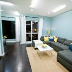 Cool Turquoise Wall Paint Of Living Room With Dark Wood Floors And Grey Sectional Sofa
