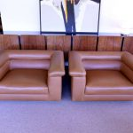 Cool and comfy brown leather lounge chairs with armrest and neckrest features